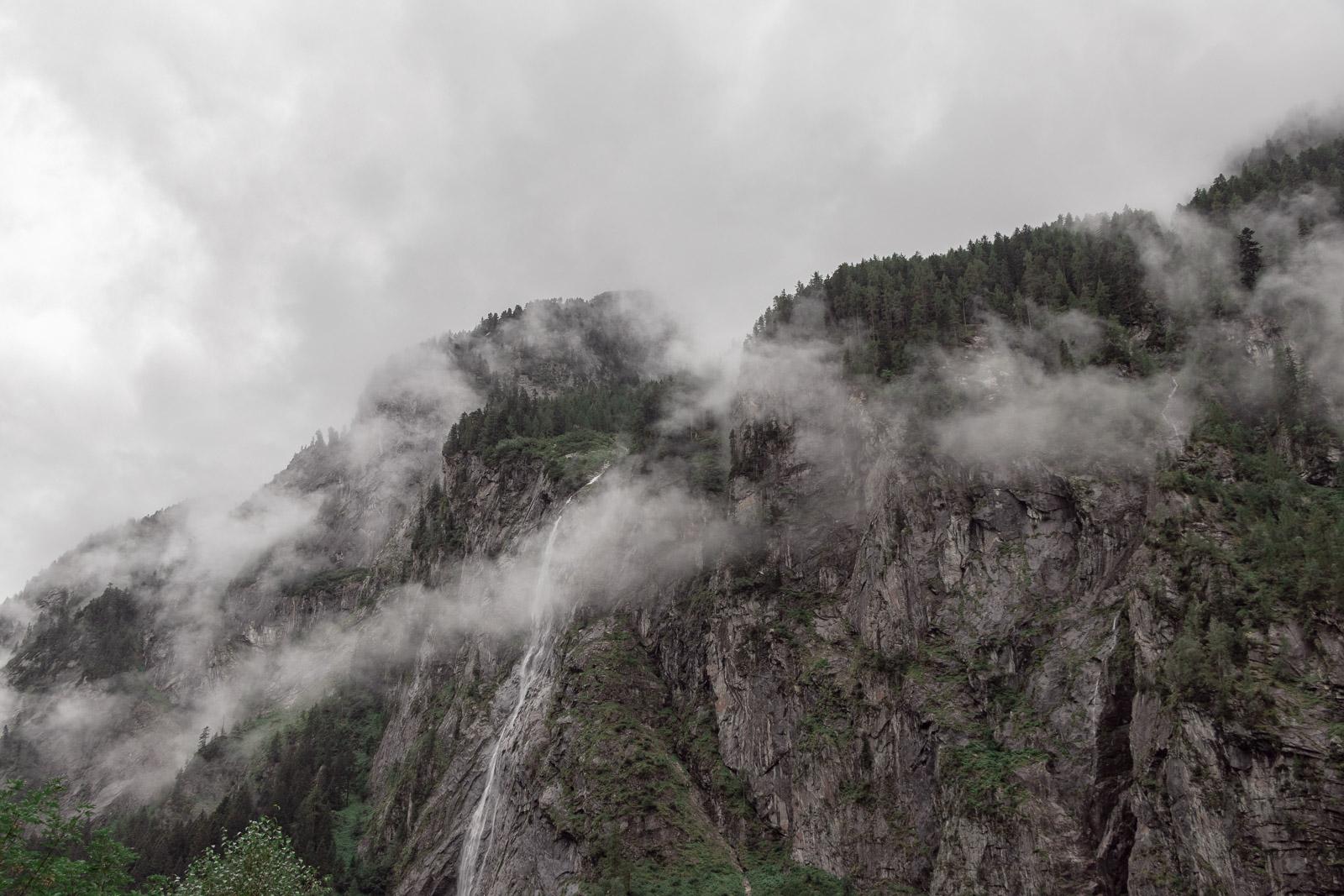 Berg mit Wasserfall, Bäumen und Nebel am Stillup Stausee